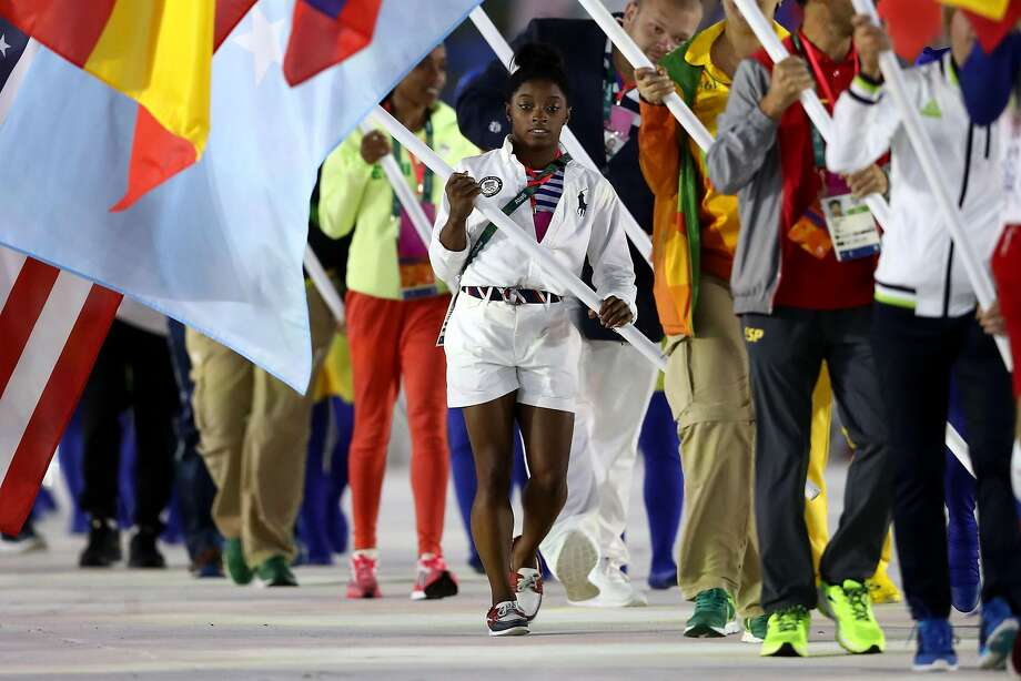 "Flag bearer Simone Biles of United States walks during the ""Heroes of the Games"" segment during the Closing Ceremony on Day 16 of the Rio 2016 Olympic Games at Maracana Stadium on August 21, 2016 in Rio de Janeiro, Brazil.  Photo: Ezra Shaw, Getty Images"
