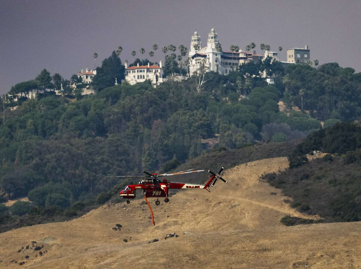 A helicopter flies past Hearst Castle on its way to fight a wildfire in San Simeon, Calif., Saturday, Aug. 20, 2016. A growing wildfire in central California has forced the closure of the historic Hearst Castle. Fire officials say the blaze was about 3 ½ miles from the hilltop estate on Saturday. (Joe Johnston/The Tribune (of San Luis Obispo) via AP)