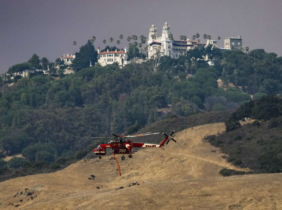 A helicopter flies past Hearst Castle on its way to fight a wildfire in San Simeon, Calif., Saturday, Aug. 20, 2016. A growing wildfire in central California has forced the closure of the historic Hearst Castle. Fire officials say the blaze was about 3 ½ miles from the hilltop estate on Saturday.  Photo: Joe Johnston, Associated Press