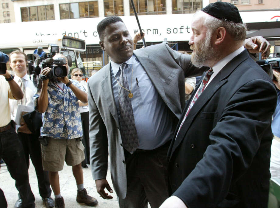FILE - In this Aug. 19, 2002, file photo, Carmel Cato, center, reaches out to embrace Norman Rosenbaum, right, as they walk together in a show of unity into a New York restaurant on the 11th anniversary of the 1991 Crown Heights riots sparked by the deaths of Cato's 7-year-old son Gavin Cato and the murder of Rosenbaum's brother Yankel, an Australian student. On Sunday, Aug. 21, 2016, residents of the Crown Heights neighborhood in Brooklyn mark the 25th anniversary of the riot. (AP Photo/Beth A. Keiser, File) ORG XMIT: NYSB721 Photo: Beth A. Keiser / AP2002