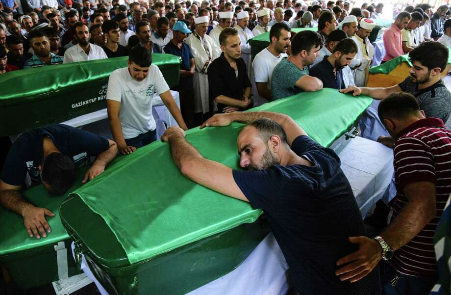 "A man bends on a coffin as people mourn during a funeral for victims of last night's attack on a wedding party that left 50 dead in Gaziantep in southeastern Turkey near the Syrian border on August 21, 2016. At least 50 people were killed when a suspected suicide bomber linked to Islamic State jihadists attacked a wedding thronged with guests, officials said on August 21. Turkish President Recep Tayyip Erdogan said the IS extremist group was the ""likely perpetrator"" of the bomb attack, the deadliest in 2016, in Gaziantep late Saturday that targeted a celebration attended by many Kurds.  / AFP PHOTO / ILYAS AKENGINILYAS AKENGIN/AFP/Getty Images ORG XMIT: 663114185 Photo: ILYAS AKENGIN / AFP or licensors"