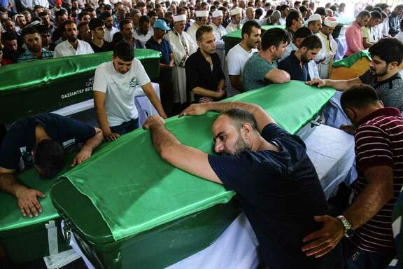 "A man bends on a coffin as people mourn during a funeral for victims of last night's attack on a wedding party that left 50 dead in Gaziantep in southeastern Turkey near the Syrian border on August 21, 2016. At least 50 people were killed when a suspected suicide bomber linked to Islamic State jihadists attacked a wedding thronged with guests, officials said on August 21. Turkish President Recep Tayyip Erdogan said the IS extremist group was the ""likely perpetrator"" of the bomb attack, the deadliest in 2016, in Gaziantep late Saturday that targeted a celebration attended by many Kurds.  / AFP PHOTO / ILYAS AKENGINILYAS AKENGIN/AFP/Getty Images ORG XMIT: 663114185"