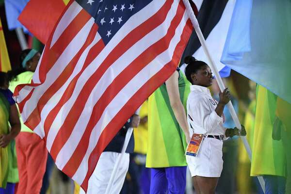 USA's flag-bearer Simone Biles holds her country's national flag during the closing ceremony of the Rio 2016 Olympic Games at the Maracana stadium in Rio de Janeiro on August 21, 2016. / AFP PHOTO / Leon NEALLEON NEAL/AFP/Getty Images