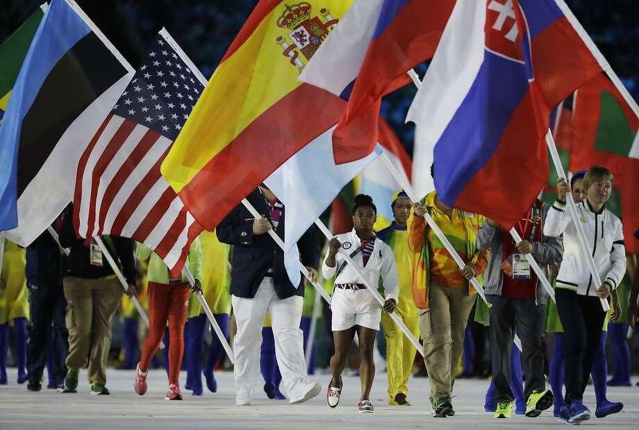 Gymnast Simone Biles (center) carries the U.S. flag during the Closing Ceremony of the Summer Olympics in Maracana Stadium in Rio de Janeiro. Photo: Matt Dunham, Associated Press