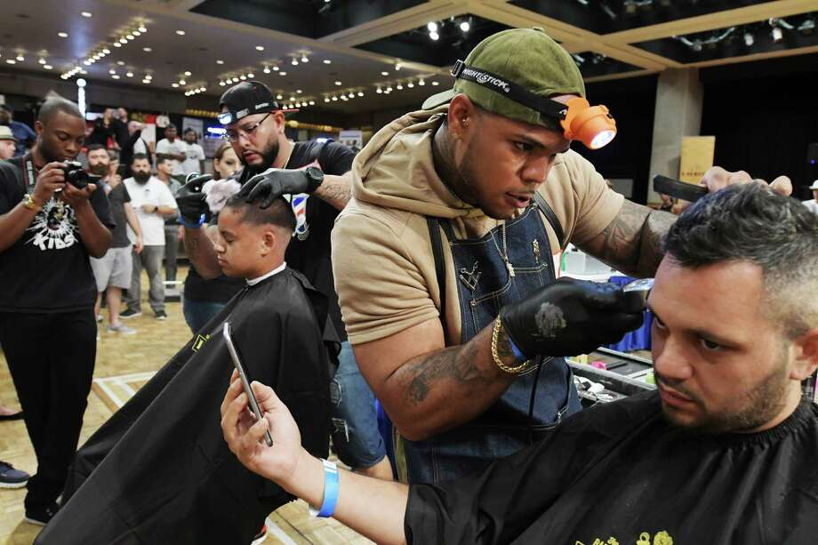 Juan Garcia, foreground, a barber with Barber's Blueprint out of Manhattan and Anthony Ramos, background, owner of Big Time Barber Shop in Indiana and Texas, compete in the fastest fade hair cutting competition at the first annual New York State Barber Expo at the Empire State Plaza Convention Center on Sunday, Aug. 21, 2016, in Albany, N.Y.  Marlon Sousis and Peter Burdick who co-own Hall of Fades Barber Shop in Rensselaer and Jason Belleville organized the expo as a way to unite the barber community in the area Sousis said.  The event featured over 60 vendors from around the country and four different barber competitions.  The event also featured educators who ran classes on marketing, branding, and various hair cutting techniques.    (Paul Buckowski / Times Union) Photo: PAUL BUCKOWSKI / 20037718A