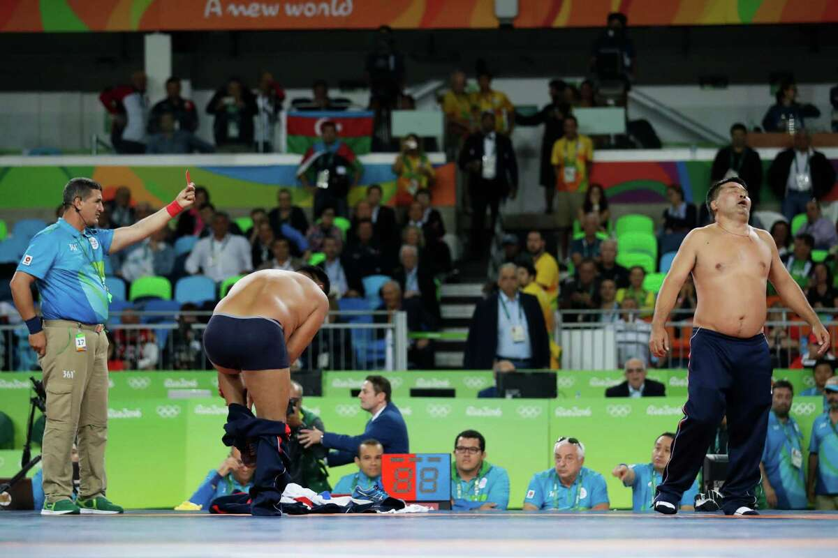 Coaches of Mongolia's wrestler Mandakhnaran Ganzorig take off their clothes in protest against the decision of the jury to award the bronze medal to Uzbekistan's Ikhtiyor Navruzov during the men's 65-kg freestyle wrestling competition at the 2016 Summer Olympics in Rio de Janeiro, Brazil, Sunday, Aug. 21, 2016. (AP Photo/Markus Schreiber)