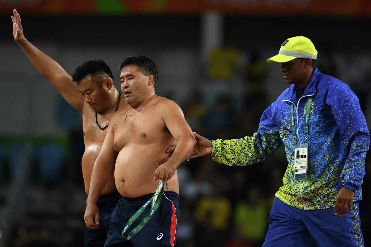 RIO DE JANEIRO, BRAZIL - AUGUST 21: Mongolias coaches protest the judges decision after Mandakhnaran Ganzorig (red) of Mongolia is defeated by Ikhtiyor Navruzov (blue) of Uzbekistan in the Men's Freestyle 65kg Bronze match against on Day 16 of the Rio 2016 Olympic Games at Carioca Arena 2 on August 21, 2016 in Rio de Janeiro, Brazil.