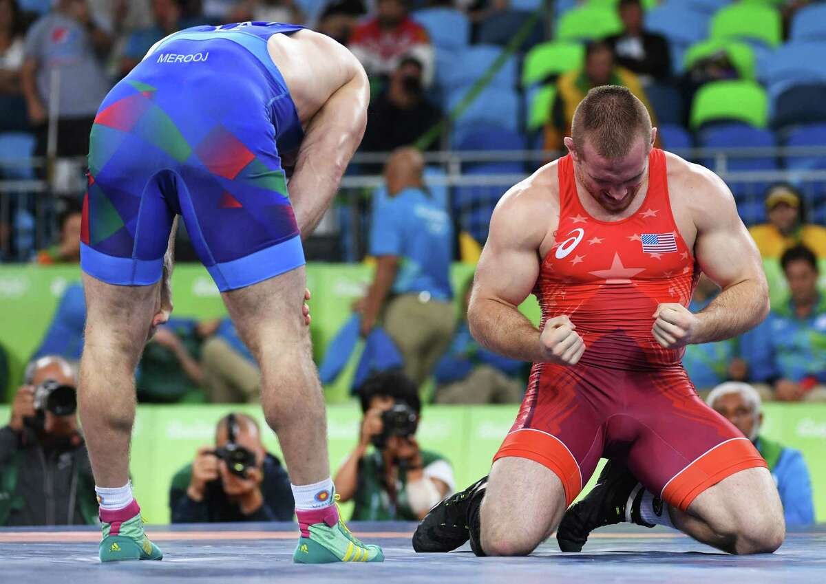 Kyle Snyder, right, starts a long-awaited celebration after holding off Azerbaijan's Khetag Gazyumov to become the youngest American to win an Olympic wrestling gold medal, doing so at 20.