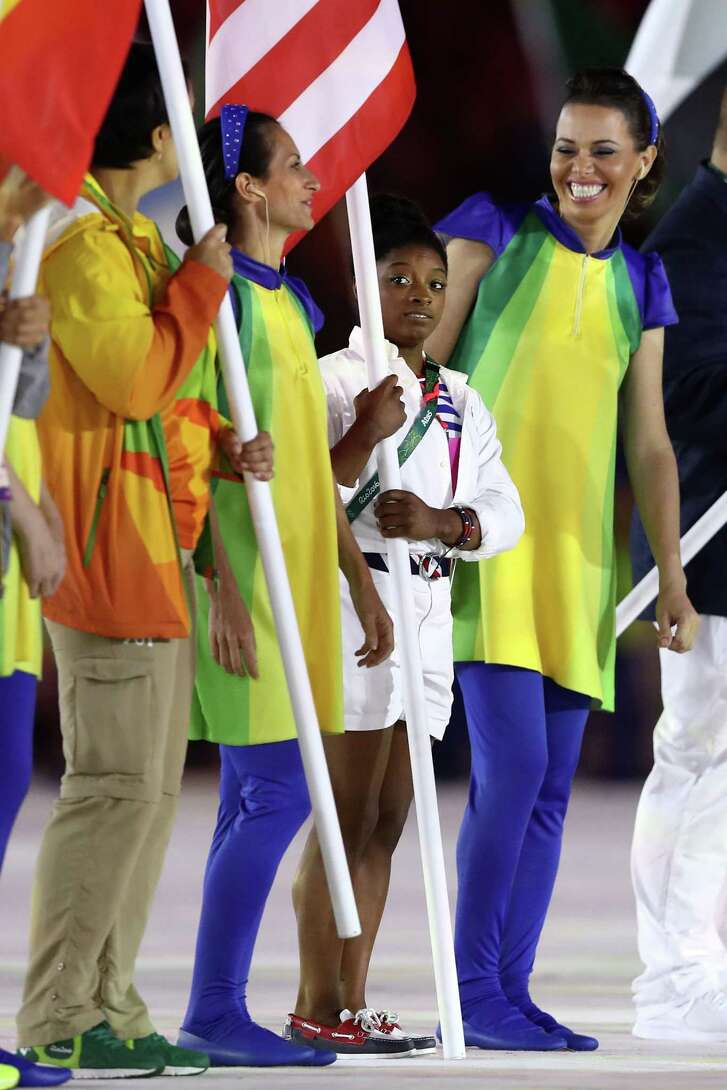 """RIO DE JANEIRO, BRAZIL - AUGUST 21:  Flag bearer Simone Biles of United States participates during the """"Heroes of the Games"""" segment during the Closing Ceremony on Day 16 of the Rio 2016 Olympic Games at Maracana Stadium on August 21, 2016 in Rio de Janeiro, Brazil.  (Photo by Ezra Shaw/Getty Images)"""