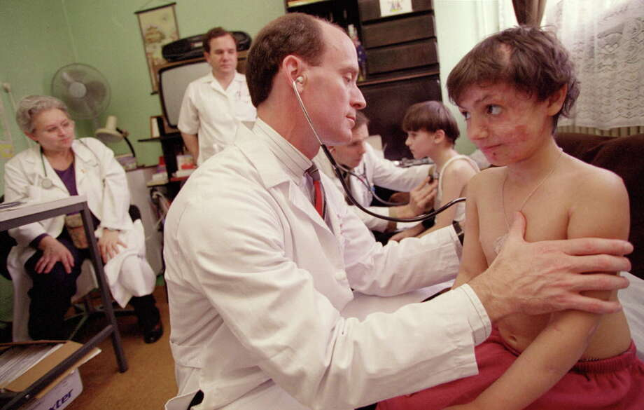 Dr. Mark Kline examines a patient in 1998 in Romania, where he would go on to found a pediatric AIDS clinic. Photo: Smiley N. Pool, HC Staff / Houston Chronicle