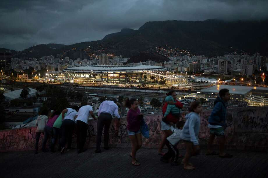People walk on a viaduct at the Mangueira slum as the Maracana stadium is lit before the closing ceremony of the Summer Olympics in Rio de Janeiro, Brazil, Sunday, Aug. 21, 2016. Photo: Felipe Dana, AP Photo / AP Photo