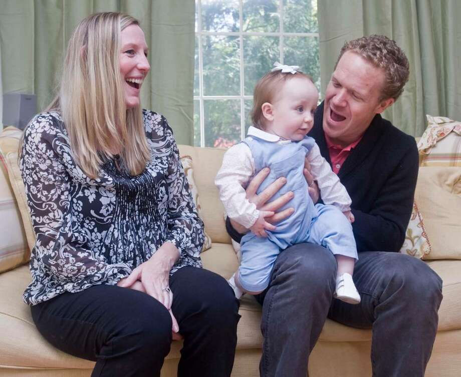 Daryn and Matt Art with 1-year-old daughter Camryn, at their home in Ridgefield. They are a couple who used holistic fertility practices to get pregnant after a couple of miscarriages and misguided medical information that suggested they might never have their own children. Friday, April 23, 2010 Photo: Scott Mullin / The News-Times Freelance