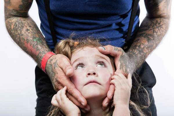 Frankie May Gonzalez looks up at her dad, Jason Gonzalez, a tattoo artist at BTU Tattoo, during the 15th annual Seattle Tattoo Expo at the Seattle Center, Sunday, Aug. 21, 2016.