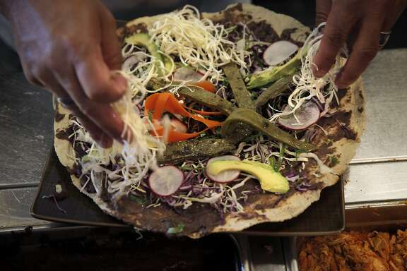 Chef Octavio Diaz of Agave Uptown prepares a vegan Tlayuda at the restaurant in Oakland, Calif., on Thursday, August 18, 2016.