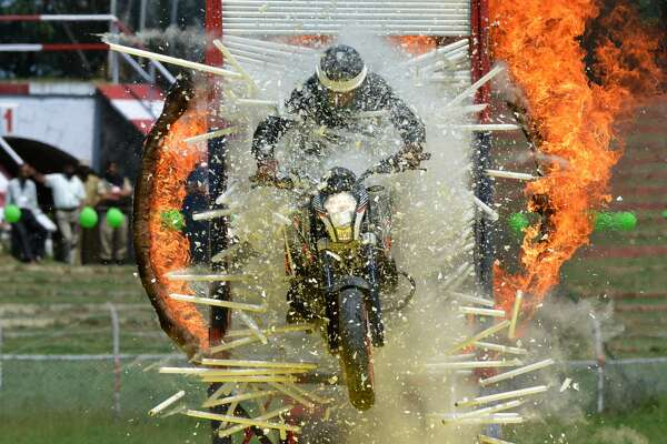 TOPSHOT - A Jammu and Kashmir Police (JKP) motorcyclist rides through a burning hoop and a wall of glass tubes during an Independence Day event at The Bakshi Stadium in Srinagar on August 15, 2016. A police paramilitary commander was shot dead in Kashmir's main city while at least two suspected separatist militants were killed in gun-battles as violence flared in the disputed Himalayan region on Indian Independence Day. The unnamed commander was critically injured in an ambush and died in hospital, a senior officer of India's Central Reserve Police Force (CRPF) confirmed to AFP, adding that two other members of the force were in a critical condition.  / AFP / TAUSEEF MUSTAFA        (Photo credit should read TAUSEEF MUSTAFA/AFP/Getty Images)