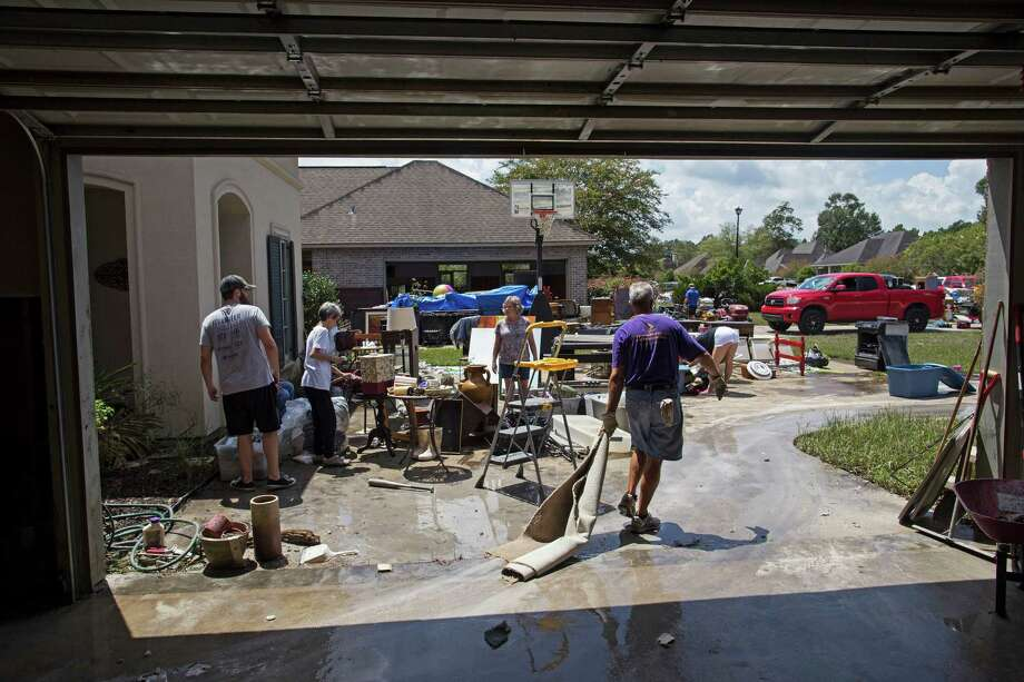 Friends and family help to clean out the flood damaged home of Sheila Siener, 58, second from left, in St. Amant, La., Saturday, Aug. 20, 2016. Louisiana continues to dig itself out from devastating floods, with search parties going door to door looking for survivors. Three American Red Cross volunteers from the Bridgeport region are deploying to Louisiana to support Red Cross relief efforts there. AP Photo/Max Becherer) Photo: Max Becherer / Associated Press / FR171354 AP