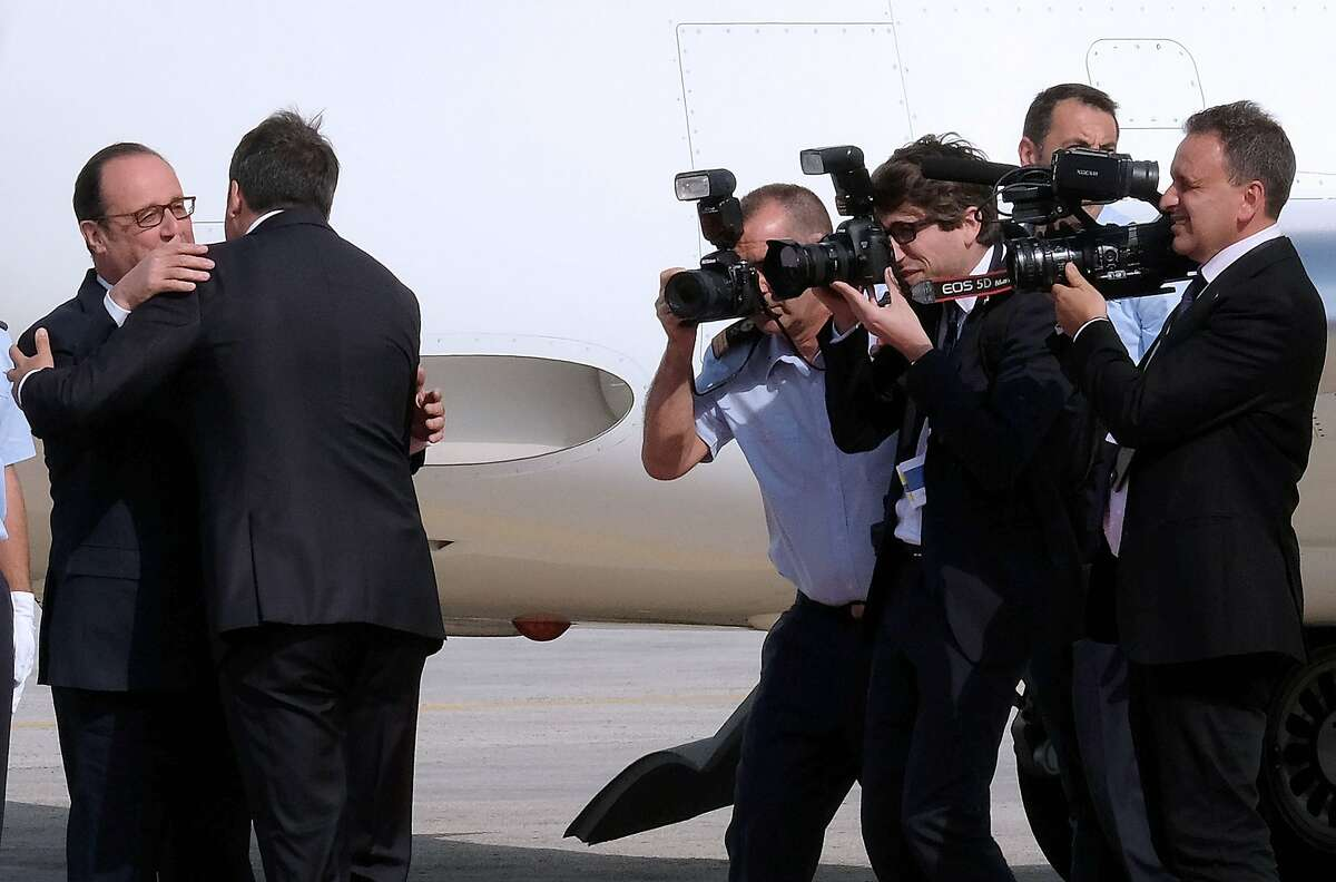 Photographers take pictures as Italian Prime Minister Matteo Renzi (2R) greets French President Francois Hollande upon their arrival at the Capodichino international airport in Naples on August 22, 2016, ahead of a meeting on the island of Ventotene, where the leaders of Italy, France and Germany meet to discuss the post-Brexit EU. Europe's economic outlook, jihadist attacks, the refugee and migrant drama, the Syrian conflict, and relations with Russia and Turkey were all on the agenda for the talks later Monday on the island of Ventotene, one of the cradles of the European dream. / AFP PHOTO / MARIO LAPORTAMARIO LAPORTA/AFP/Getty Images