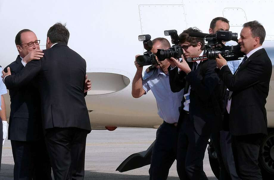 Photographers take pictures as Italian Prime Minister Matteo Renzi (2R) greets French President Francois Hollande upon their arrival at the Capodichino international airport in Naples on August 22, 2016, ahead of a meeting on the island of Ventotene, where the leaders of Italy, France and Germany meet to discuss the post-Brexit EU. Europe's economic outlook, jihadist attacks, the refugee and migrant drama, the Syrian conflict, and relations with Russia and Turkey were all on the agenda for the talks later Monday on the island of Ventotene, one of the cradles of the European dream. / AFP PHOTO / MARIO LAPORTAMARIO LAPORTA/AFP/Getty Images Photo: MARIO LAPORTA, AFP/Getty Images