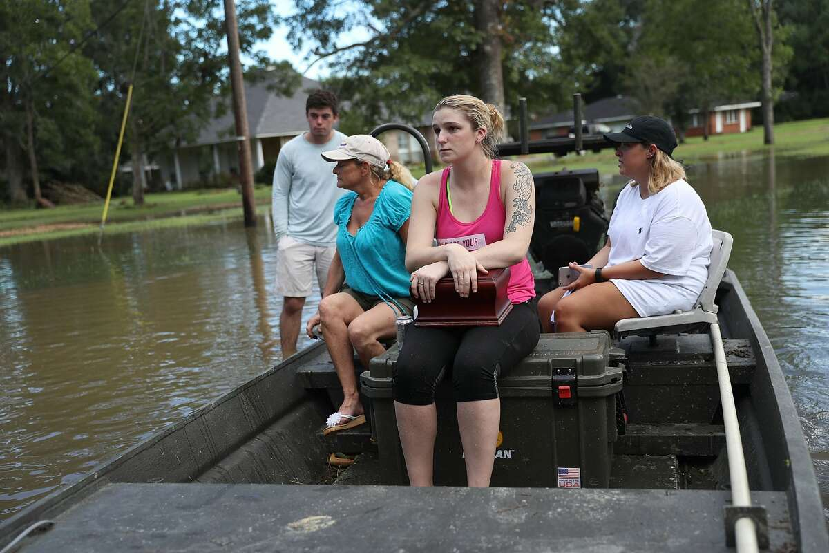 BATON ROUGE, LA - AUGUST 15: Allie Amond holds a box with her father's ashes in it that she retrieved from her flooded home on Aug. 15, 2016, in Baton Rouge, La. Record-breaking rains pelted Louisiana over the weekend leaving the city with historic levels of flooding that have caused at least seven deaths and damaged thousands of homes. (Photo by Joe Raedle/Getty Images)