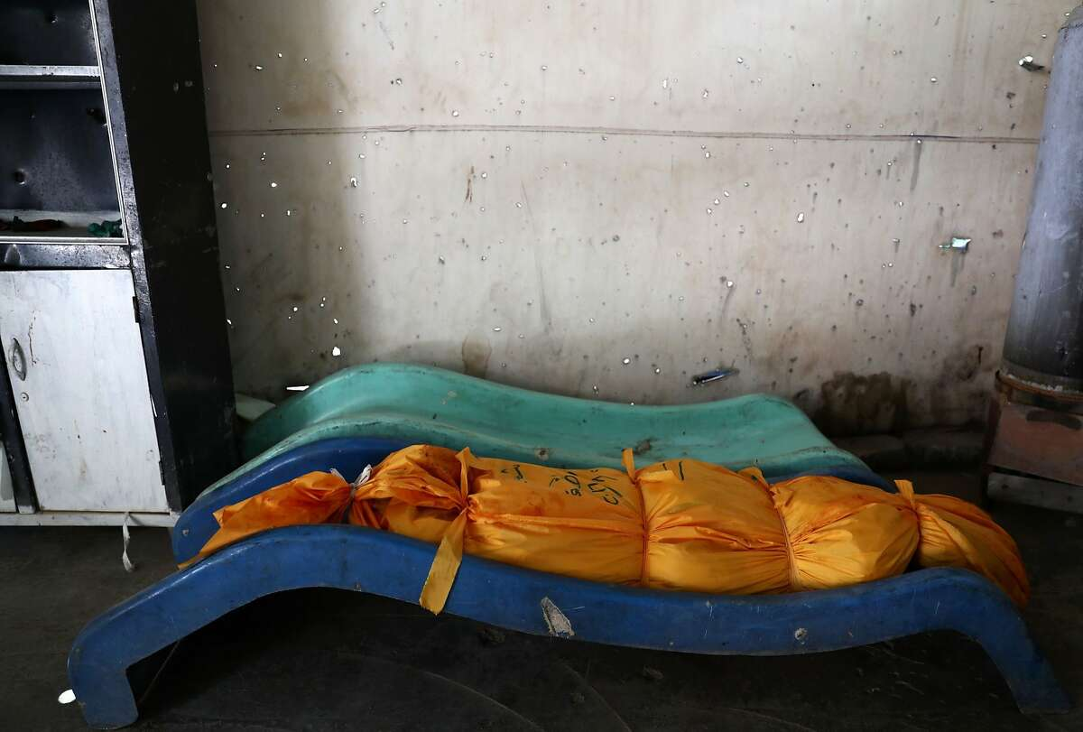 A body wrapped in shrouds is seen lying on a children's slide at a make-shift morgue following reported air strikes on the rebel-held town of Douma on August 22, 2016. / AFP PHOTO / Abd DoumanyABD DOUMANY/AFP/Getty Images