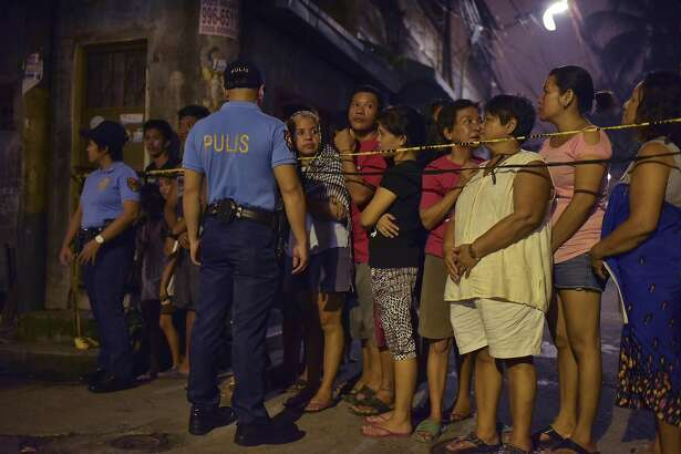 Police officers guard the perimeter of a scene where two  alleged drug dealers were reportedly killed by police, in Manila, Philippines, Aug. 19, 2016. Killings by the police and vigilantes in the Philippines� war on drugs have soared to nearly 1,800 in the seven weeks since President Rodrigo Duterte was sworn into office, according to the nation's top police official. (Jes Aznar/The New York Times)