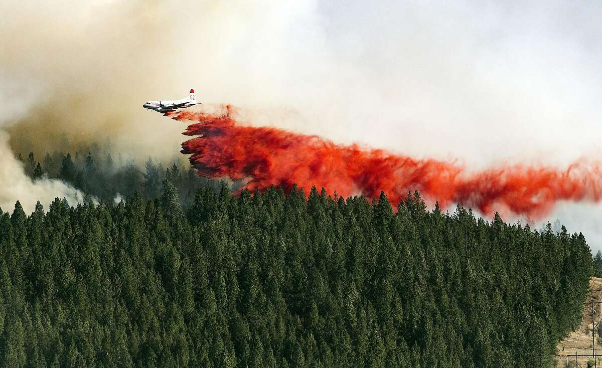 A plane drops a load of fire retardant on the north side of Beacon Hill, Sunday, Aug 21, 2016, in Spokane, Wash. The fast moving wildfire is threatening structures as it moves in a north-easterly direction. (Colin Mulvany/The Spokesman-Review, via AP)
