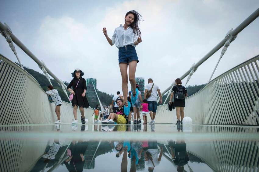 A visitor jumps for a photograph on the world's highest and longest glass-bottomed bridge above a valley in Zhangjiajie in China's Hunan Province on August 21, 2016.