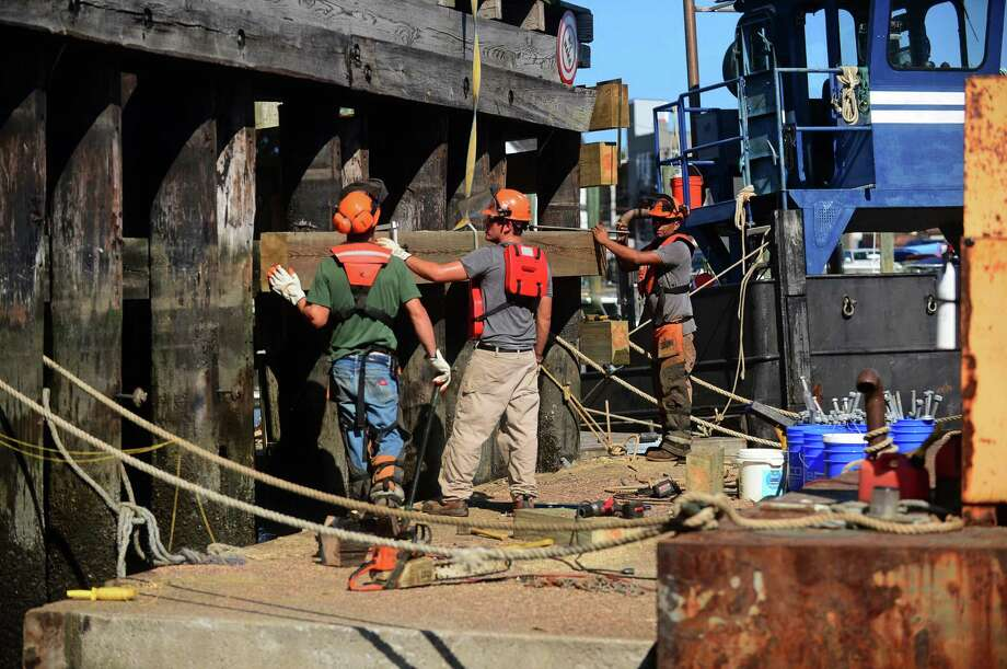 Workers repair the fenders surrounding the piers of the Walk Bridge Thursday, August 18, 2016. The Connecticut Department of Transportation plans to upgrade rails and catenary lines and build new dockyard in 2017 as part of runup to start of Walk Bridge replacement in mid-2018. Photo: Erik Trautmann / Hearst Connecticut Media / Norwalk Hour
