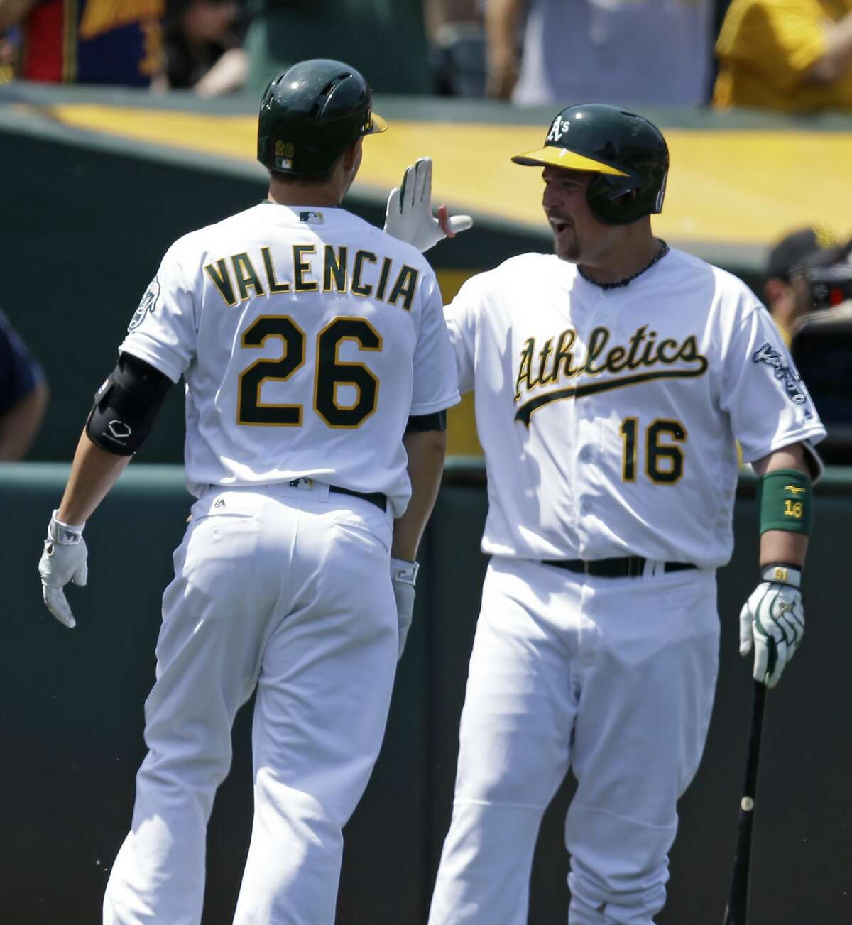 Oakland Athletics' Danny Valencia, left, is congratulated by Billy Butler (16) after hitting a home run off Detroit Tigers' Matt Boyd in the fourth inning of a baseball game Saturday, May 28, 2016, in Oakland, Calif.