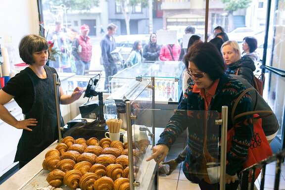 A customer orders a croissant at Arsicault Bakery in S.F.
