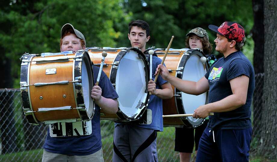 Nathan Sprock, 14, left, Michael Lopez, 17, and Creston Craig, 14, practice the base drum with the guidence of instructor Andrew Zwart, right, Monday morning, August 22, 2016, at Bethel High School's band camp. Public schools in Bethel open Wednesday, August 31. Photo: Carol Kaliff, Hearst Connecticut Media / The News-Times