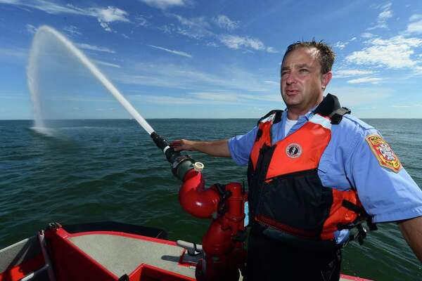 Norwalk Fire Department Captain Jon Maggio demonstrates the bow monitor, which shoots water approximately 25 meters, as he gives a tour of the Department's Marine Unit 238, a North River Hybrid Response Boat, Wednesday, Aug. 17, 2016, in Norwalk, Conn. The marine units respond year-round to incidents and emergencies in and around Norwalk Harbor as well as Long Island Sound and will have a role in the safety duties for the Metro-North Railroad Walk Bridge replacement.