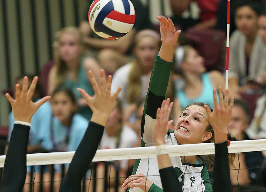 Rattler Camryn Ennis elevates over Morgan Vacek and Ashlyn Teis (15) as Reagan plays Churchill at Littleton Gym on Sept. 22, 2015. Photo: Tom Reel /San Antonio Express-News