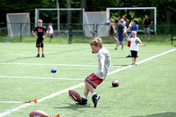 Charlie O'Neil, 7, punts the ball during the NFL Punt, Pass and Kick Competition held at the Water Tower Field at Waveny Park in New Canaan on aUG. 19, 2016.