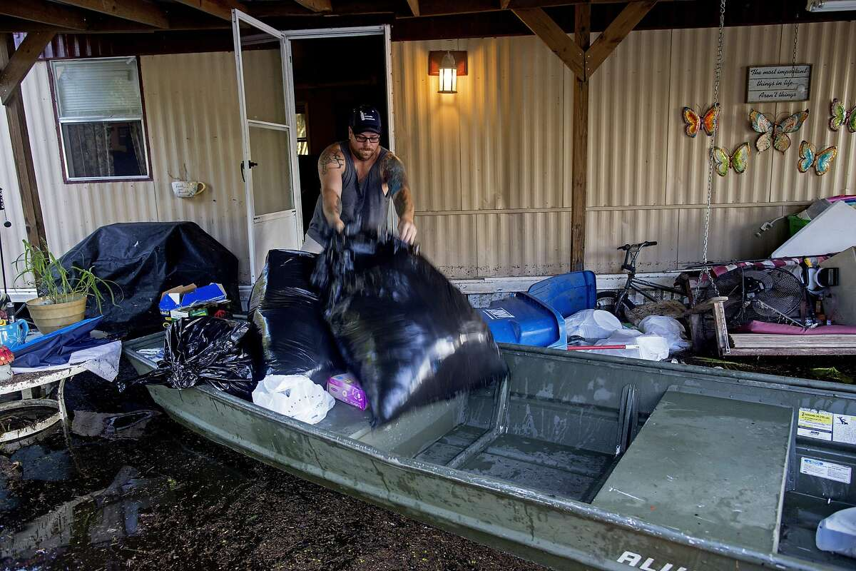 Giovanni DeCarlo, 35, loads a bag of clothes on a boat as he helps friend Laura Albritton, salvage personal belongings from her flooded home in Sorrento, La., Saturday, Aug. 20, 2016. Louisiana continues to dig itself out from devastating floods, with search parties going door to door looking for survivors or bodies trapped by flooding. (AP Photo/Max Becherer)