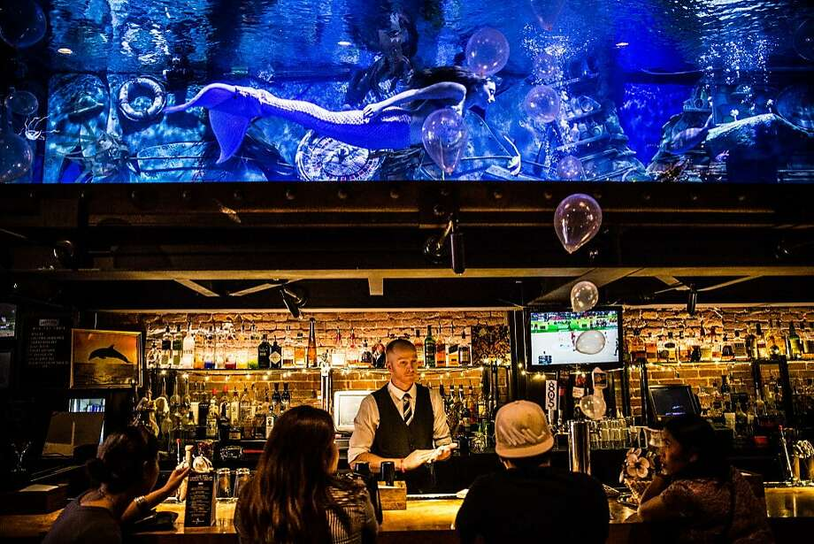 A mermaid swims in the huge aquarium of the Dive Bar in Downtown Sacramento. Photo: Max Whittaker/Prime, Special To The Chronicle