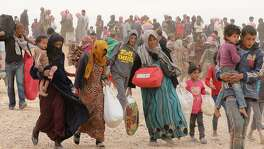 "(FILES) This file photo taken on May 4, 2016 shows Syrian refugees carrying their belongings as they wait to enter Jordanian side of the Hadalat border crossing, a military zone east of the capital Amman, after arriving from Syria.  Jordan's King Abdullah II has rejected calls to restore access to a border area where tens of thousands of Syrians are stranded, local media reported on August 15. Jordan declared the area around the Rukban border crossing a ""closed military zone"" in June, after a suicide bombing claimed by the Islamic State group killed seven soldiers near a makeshift desert camp where more than 100,000 Syrians are stuck.  / AFP PHOTO / KHALIL MAZRAAWIKHALIL MAZRAAWI/AFP/Getty Images"