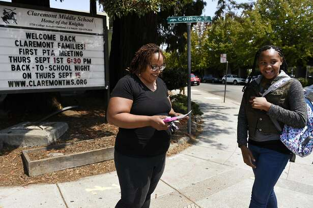 Robin Frazier talks with her daughter Nasrani Fanny while picking her up after her first day of sixth grade at Claremont Middle School in Oakland, CA Monday, August 22, 2016.