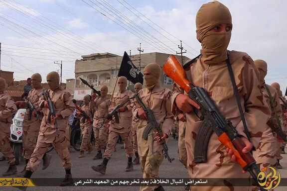 "Young boys known as the ""cubs of the caliphate"" march after graduating from a religious school in Tal Afar, northern Iraq. Islamic State has a history of using children as weapons, sending them to their death strapped with explosives and putting them on front lines in Iraq and Syria."