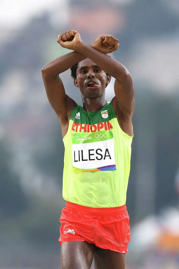 RIO DE JANEIRO, BRAZIL - AUGUST 21:  Feyisa Lilesa of Ethiopia celebrates as he crosses the line to win silver during the Men's Marathon on Day 16 of the Rio 2016 Olympic Games at Sambodromo on August 21, 2016 in Rio de Janeiro, Brazil.  (Photo by Matthias Hangst/Getty Images) ORG XMIT: 631447909 Photo: Matthias Hangst / 2016 Getty Images