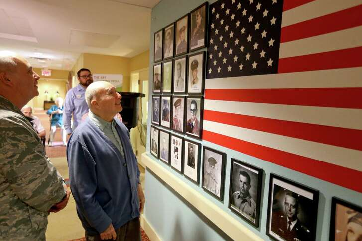 Twenty-Fifth Air Force senior chaplain Col. Bruce R. Glover (left) and Villa de San Antonio resident Elias Hill, 90, look at a veterans wall to honor Villa de San Antonio residents who served in the military during the unveiling Monday Aug. 22, 2016. Hill was a paratrooper in the Army during World War II.
