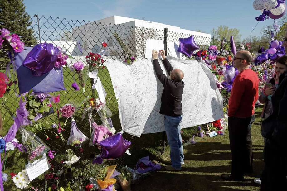 FILE - In this April 22, 2016, file photo, a fan writes a note at the memorial fence in memory of pop star Prince at Paisley Park Studios in Chanhassen, Minn. A hearing will be held Monday, June 27, 2016, in suburban Minneapolis about the procedures for determining who stands to inherit part of Prince's estate. Prince died in April of an accidental drug overdose, and no will has been found. (AP Photo/Jim Mone, File) ORG XMIT: MP803 Photo: Jim Mone / Copyright 2016 The Associated Press. All rights reserved. This m