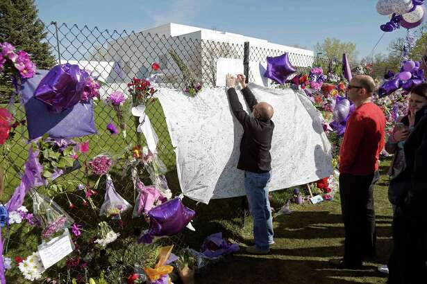 FILE - In this April 22, 2016, file photo, a fan writes a note at the memorial fence in memory of pop star Prince at Paisley Park Studios in Chanhassen, Minn. A hearing will be held Monday, June 27, 2016, in suburban Minneapolis about the procedures for determining who stands to inherit part of Prince's estate. Prince died in April of an accidental drug overdose, and no will has been found. (AP Photo/Jim Mone, File) ORG XMIT: MP803