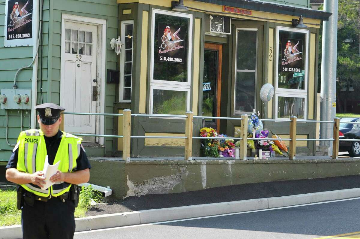 Colonie Police patrolman Thomas Breslin and other members of the Colonie Police Department hand out flyers in front of Recycled Salon on Tuesday, Aug. 25, 2015, in Colonie, N.Y. Jacquelyn Porreca was stabbed inside the business and died from her injuries. (Paul Buckowski / Times Union archive)