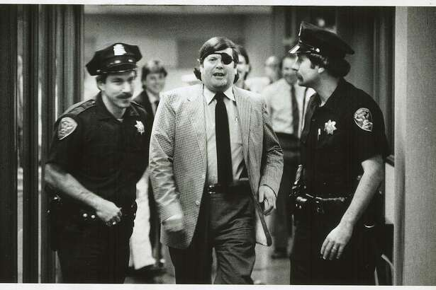 Warren Hinckle is arrested by officers Marty Sacco (left) and Ross Laflin at The Chronicle in 1985.