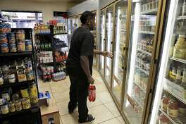 Stephon Nelson picks up a two-liter Sunkist soda at South Berkeley Meat & Produce store in Berkeley, Calif., on Monday, August 22, 2016. A new UC-Berkeley study shows that Berkeley's first-of-its-kind-in-the-nation tax on sodas and other sugary drinks has led to a drop in soda consumption in the city's most low-income neighborhoods.