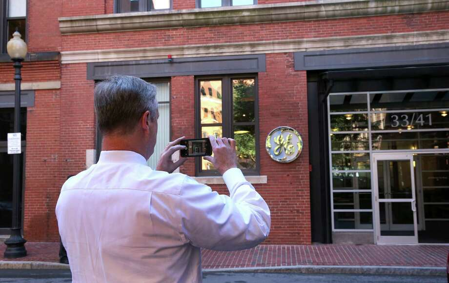 Gov. CharlIe Baker takes a photo of the GE entrance. General Electric has opened its new headquarters in Fort Point on Farnsworth Street in Boston, Aug. 22, 2016. Photo: Boston Globe, Boston Globe Via Getty Images / Getty Images