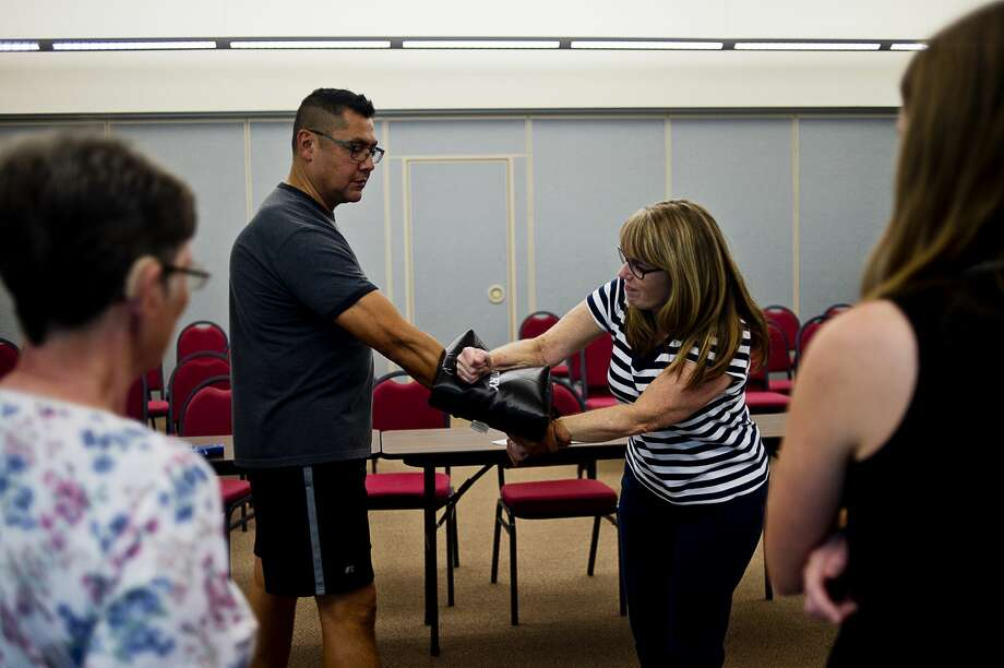 "Instructor and Secure Solution owner Henry Reyna, left, teaches Saginaw resident Anne Coursey how to punch an intruder in a pressure point during the ""Responding to Acts of Violence: Women's Self Defense"" class on Tuesday at the Great Lakes Safety Training Center. Reyna, who had experience as a law enforcement officer, taught women how to avoid and fight back in harmful situations while also providing background on various self-defense tools. Photo: Erin Kirkland/Midland Daily News"