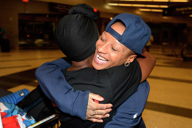 Inika McPherson hugs Erica DeBato after she arrives home from the Rio Olympics at the George Bush International Airport in Houston on Tuesday morning.  Photo taken Tuesday 8/23/16 Ryan Pelham/The Enterprise
