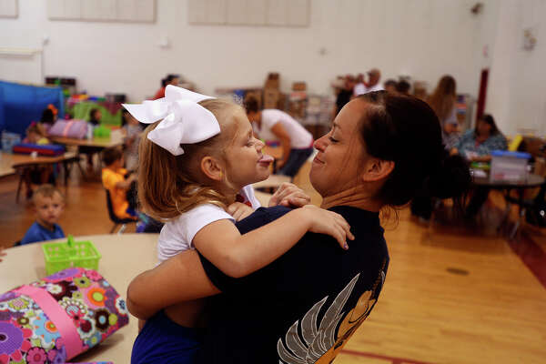 Bryley Strickland plays with her mom, Misty, before being dropped off for the first day of pre-k in Deweyville on Monday. The town's elementary students are still at the high school until the new portable classrooms are ready.  Photo taken Monday 8/22/16 Ryan Pelham/The Enterprise